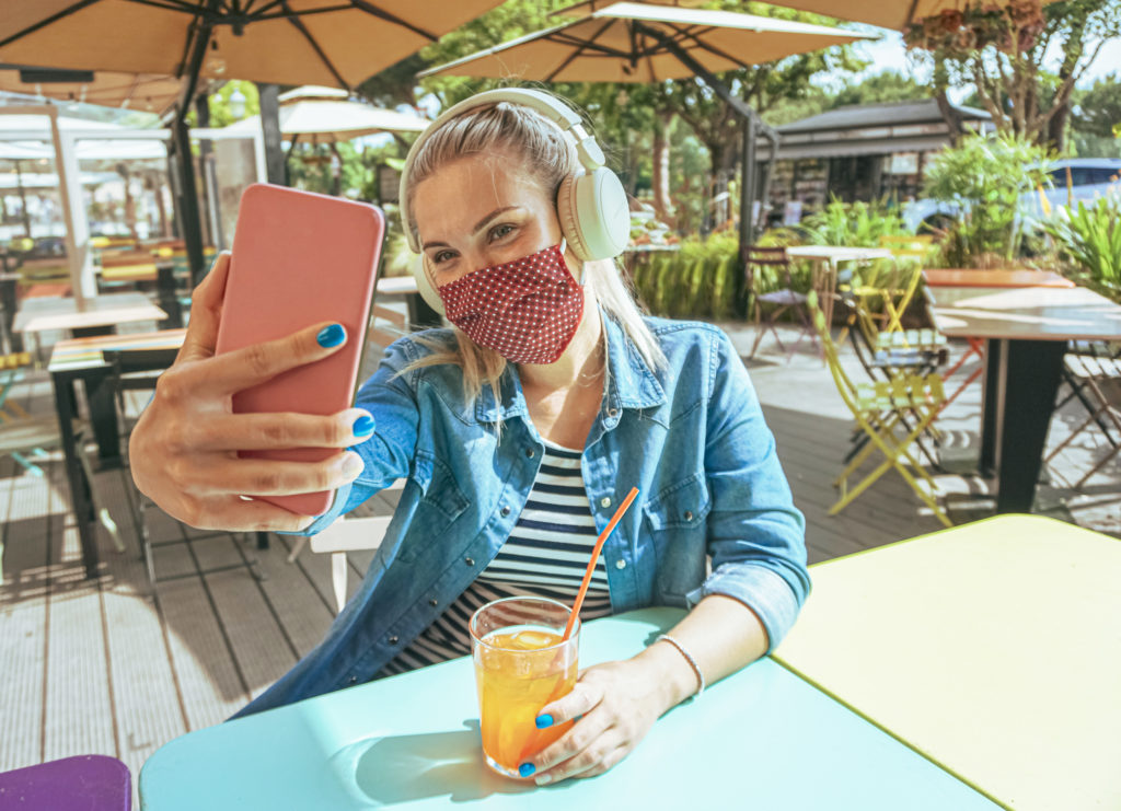 Girl in bar taking a selfie with a smartphone with her face mask on as a protection for coronavirus time.